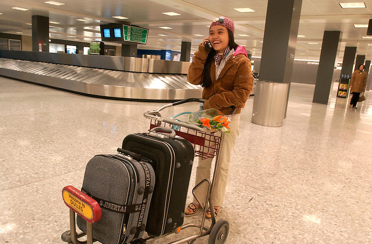 Thuy Anh speaks to Chuck Atkins on the phone at Dulles Airport after she arrived from Vietnam.  Chuck went looking for her because it was believed she was lost.
