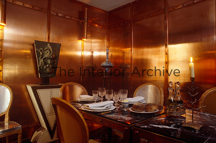The walls of this dining room are lined with riveted copper panels