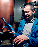 SWITZERLAND, Couvet, Absinthe maker Claude-Alain Bugnon holding a bottle at his Artemisia Distillerie, Jura Region