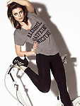 Portrait of a young woman wearing a humorous T-shirt listing bad habits, standing near an exercise bike isolated on white background