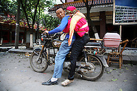 A man looks back at his dead wife, strapped to himself on a motorcycle, in Hanwang, Sichuan, China on 14 May 2008. Rescue workers have given up on finding people still alive and began to use heavy machinery.
