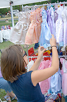 Woman shopping for toddler dresses at outdoor concession stand. Aquatennial Beach Bash Minneapolis Minnesota USA