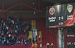 Sheffield United 2 Leeds United 0, 19/03/2011. Bramall Lane, Championship. Leeds United supporters in the away end next to the electronic scoreboard at  Bramall Lane watching the second half action during the Npower Championship fixture against Sheffield United. The home team won the game by two goals to nil watched by a crowd of 23,728. Bramall Lane is the world's oldest professional football ground and at one time hosted both football and cricket. Photo by Colin McPherson.