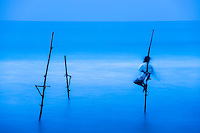 Long exposure, motion blur photo of a stilt fisherman at Midigama near Weligama, South Coast, Sri Lanka, Asia. This is a long exposure, motion blur photo of a stilt fisherman at Midigama near Weligama, South Coast, Sri Lanka, Asia. By using a technique of long exposure photography, the waves become a glassy blur.