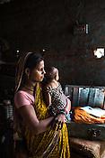 Maina Devi seen with her 3 month old daughter, Priya in their hut in Bhelaiya village in Raxaul, Bihar, India.