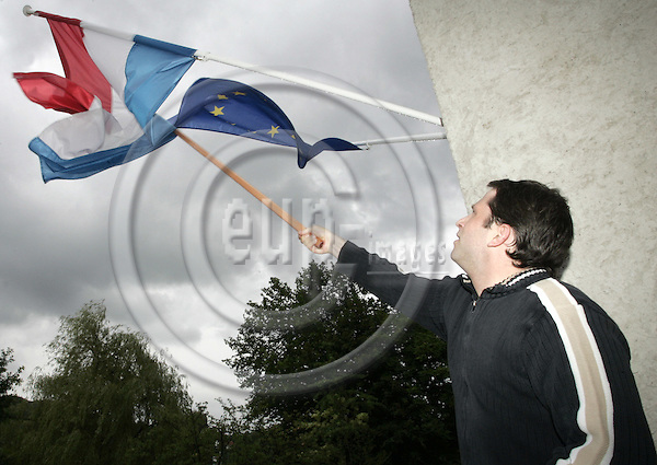 LUXEMBOURG - SCHENGEN 07 MAY 2003 -- The referendum on the EU Constitution in Luxembourg.-- Laurent THINNES will vote YES on the constitution. He works at the Europe-Direct center. Laurent unwrapping the twisted flag of Luxembourg at the center.--PHOTO: JUHA ROININEN