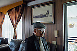 Dang Van Au poses for a portrait next to a photo of a C130 plane in his home in Westminster, California, March 26, 2016. <br /> <br /> Photo by Kendrick Brinson