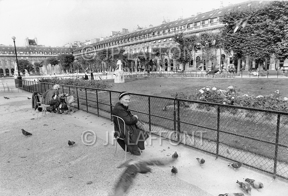 Paris, August 1977. Jardin Palais Royal. August in Paris is a noveable feast. While millions of residents are leaving for their favourite resorts, thousands of foreign tourists are flocking to the French Capital. Nevertheless, genuine Parisians, old and young alike, stay in Paris and mantain the tradition charm.