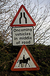 Oncoming vehicles in middle of road, horses, narrowing road signs