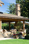 a covered porch and patio on the end of this large, lodge like estate sized home boasts outdoor seating and dining and a large masonry fireplace and chimney to make great outdoor living space under a sunny blue sky