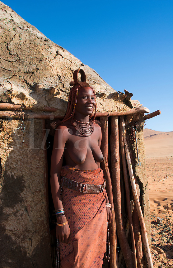Namibia Africa remote nomadic Himba tribe young woman portrait in front of hut home in desert with traditional dress in desert of Hartmann Berge in Namib Desert topless breasts of black girl