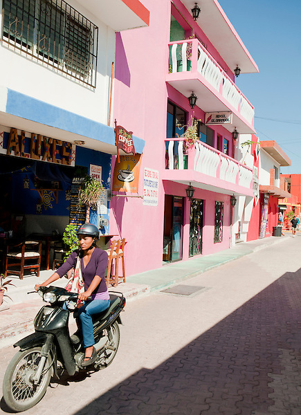 A Mexican woman rides a moped through downtown Isla Mujeres.  Isla Mujeres, Quintana Roo, Mexico.