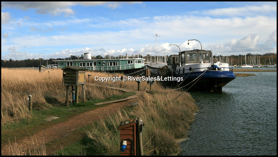 BNPS.co.uk (01202 558833)<br /> Pic: RiverSales&Lettings/BNPS<br /> <br /> ****Please use full byline****<br /> <br /> A 100-year-old barge once used to ship cargo up and down the River Thames has been transformed into a plush four-bedroom house that is now on the market for £450,000.<br /> <br /> The 90ft boat was salvaged from the banks of Thames in the 1970s and turned into a floating dormitory for schoolchildren at an outdoor activity centre.<br /> <br /> But it has since been given a complete makeover and now looks more like a cosy country cottage than a boat.<br /> <br /> The two-storey houseboat runs off mains electricity, has wifi access, electric heating, and hot water, and it also has a reserve water tank stored in its funnel.<br /> <br /> And buyers can count the picturesque River Hamble near Southampton, Hants, as their back garden.