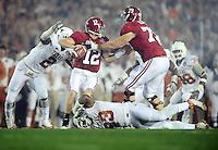 Jan 7, 2010; Pasadena, CA, USA; Alabama Crimson Tide quarterback Greg McElroy (12) is sacked by Texas Longhorns defensive end Sergio Kindle (2) and defensive tackle Lamarr Houston (33) during the first quarter of the 2010 BCS national championship game at the Rose Bowl.  Mandatory Credit: Mark J. Rebilas-