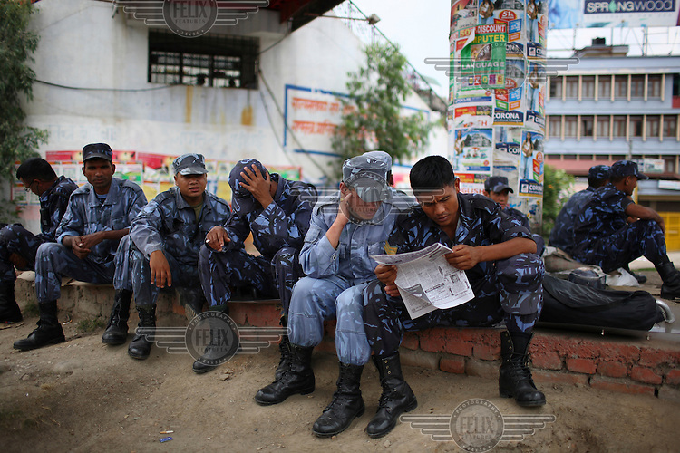 Police read a newspaper during a strike in Kathmandu.