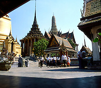 School children and tourists walking through the Grand palace in Bankok, Thailand.