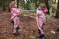 Adele Miroite, 3, left and Geneve Timmerman, right, play telephone at Fiddleheads Forest School, a nature preschool located in the UW Botanic Gardens Washington Park Arboretum.