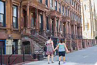 A group of brownstones on a block in the Harlem neighborhood of New York on Sunday, Jun 23, 2013.  (© Frances M. Roberts)