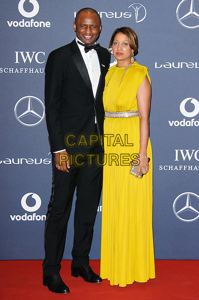 Patrick Vieira and Cheryl Vieira.Arrivals at the Laureus 2012 World Sports Awards held at the Queen Elizabeth II Centre, London, England..February 6th, 2012.full length black tuxedo yellow dress.CAP/CJ.©Chris Joseph/Capital Pictures.
