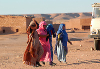 People walk on December 14, 2003, in the Saharawi refugee camps. Saharawi people have been living at the refugee camps of the Algerian desert named Hamada, or desert of the deserts, for more than 30 years now. Saharawi people have suffered the consecuences of European colonialism and the war against occupation by Moroccan forces. Polisario and Moroccan Army are in conflict since 1975 when Hassan II, Moroccan King in 1975, sent more than 250.000 civilians and soldiers to colonize the Western Sahara when Spain left the country. Since 1991 they are in a peace process without any outcome so far. (Ander Gillenea / Bostok Photo)