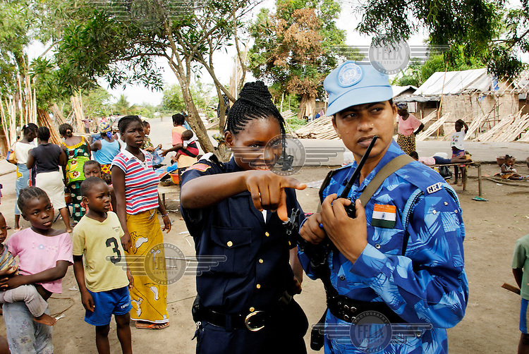 "LIBERIA, Monrovia, 05/04/2007..Winnefred, a Liberian National Police officer, and Varsha discuss potential problems in the area whilst on Joint Task Force patrol in the Duport Rd area of Monrovia. ""On the Job"" training forms a vital aspect of the unit's role in helping to build capacity in the Liberian National Police Force...© 2007 Aubrey Wade. All rights reserved."