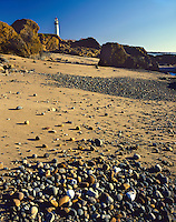 Rock-covered beach below the Pigeon point Lighthouse on the Pacific Ocean; Highway 1, CA