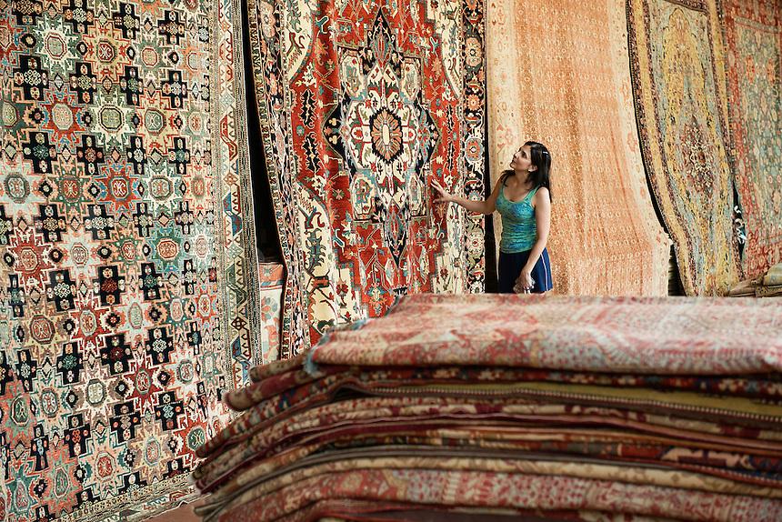 Woman shopping for an oriental carpet.