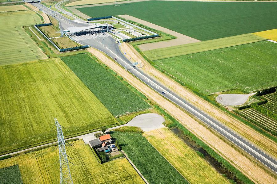 Nederland, Zuid-Beveland, Borssele polder, 04-07-2006; luchtfoto : Westerscheldetunnel, zicht op het tolplein (linksboven), de weg gaat richting tunnelingang (rechtsonder, buiten beeld), aan weerszijden van deze toegangsweg zijn geluidswallen gebouwd om geluidsoverlast te voorkomen; deze geluidsschermen zijn in de vorm van dijken, passend in het omringende landschap (landschappelijke inpassing); de lokale weg die doorsneden wordt heeft keerplaatsen gekregen; landschapsarchitectuur, planologie, verkeer en vervoer, mobiliteit, auto, infrastructuur, milieu; zie ook andere (lucht)foto's van deze lokatie, deevan de serie Panorama Nederland<br />  luchtfoto (toeslag); aerial photo (additional fee required); .foto Siebe Swart / photo Siebe Swart