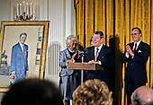 United States President George H.W. Bush officiates at the presentation of the official portraits of former U.S. President Ronald Reagan and first lady Nancy Reagan  in the East Room of the White House in Washington, D.C. on November 15, 1989.  From left to right: Barbara Bush, Nancy Reagan (partially obscured), former President Reagan, President Bush.<br /> Credit: Ron Sachs / CNP