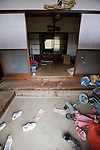 The front door is left ajar and clothing still hangs in the front room six weeks after residents were forced to leave Naruha, a small farming town that lies within the evacuation zone around the leaking No. 1 nuclear power plant in  Fukushima Prefecture, Japan on Wednesday 20 April  2011. As of April 21, Japan has made it illegal to enter the 20 km (12 mile) zone..Photographer: Robert Gilhooly