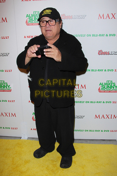 "DANNY DeVITO.""It's Always Sunny In Philadelphia : A Very Sunny Christmas"" DVD Release Party  held at Guys and Dolls Lounge, Los Angeles, California, USA..November 12th, 2009.full length black jacket trousers glasses camera taking picture photograph hat baseball cap .CAP/ADM/TC .©T. Conrad/AdMedia/Capital Pictures."