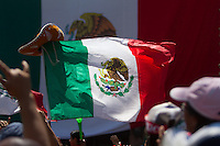 Los Angeles, CA -  Monday, June 23, 2014: A large Mexico flag waves as hundreds of Mexico fans watch the Mexico vs. Croatia first round match at a public viewing at Plaza Mexico.