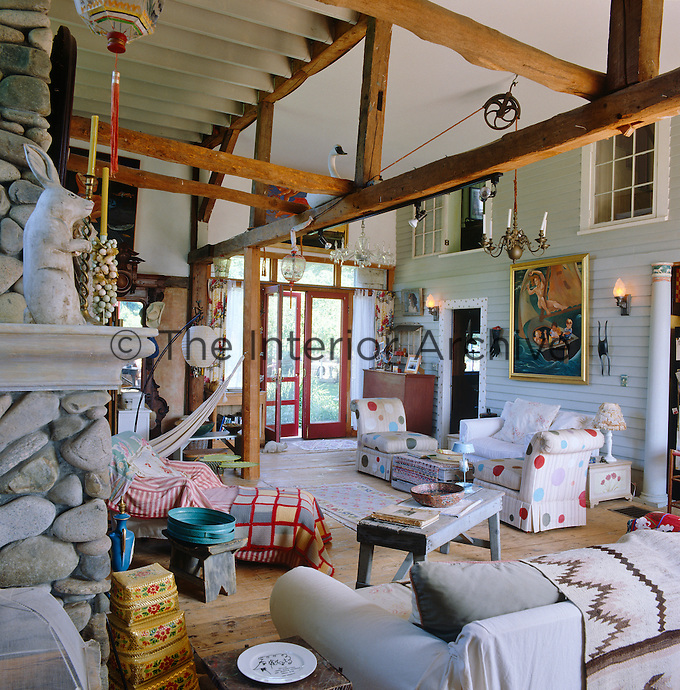 General view of the open-plan living area which has been furnished with a variety of chairs found in local sales.  The painting is by the owner Edie Vonnegut