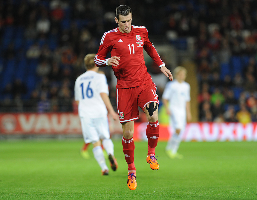 Wales Gareth Bale feels the impact of a tackle <br /> <br /> Photo by Ashley Crowden/CameraSport<br /> <br /> Football - International Friendly - Wales v Finland - Saturday 16th November 2013 - Cardiff City Stadium - Cardiff<br /> <br /> &copy; CameraSport - 43 Linden Ave. Countesthorpe. Leicester. England. LE8 5PG - Tel: +44 (0) 116 277 4147 - admin@camerasport.com - www.camerasport.com