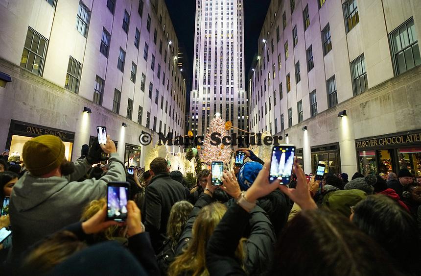 Besucher machen Handyfotos vom Weihnachtsbaum und dem Rockefeller Center in New York - 08.12.2019: New York