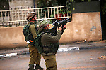 An Israeli soldier fires tear gas towards Palestinian protesters during clashes next to the Jewish settlement of Psagot, near the West Bank city of Ramallah, November 3, 2015. The current wave of violence erupted in mid-September, fueled by rumors that Israel was trying to increase Jewish presence in Jerusalem then quickly spread across Israel, the West Bank and the Gaza Strip. Photo by Shadi Hatem