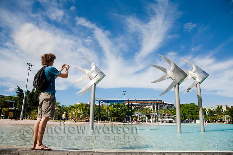 Tourist photographing the Fish Sculpture at the Esplanade lagoon.  Cairns, Queensland, Australia