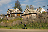 A schoolboy passes .traditional wooden houses in the Carpathian village of Mikulicyn (Mikulycyn) in south-western Ukraine.