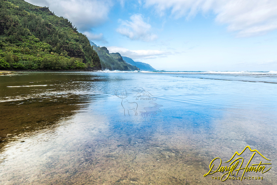 The Napali Coast as seen from Ke'e Beach on the island of Kauai Hawaii.  This reef made a large waveless flat which made possible a slight reflection of coast and sky.