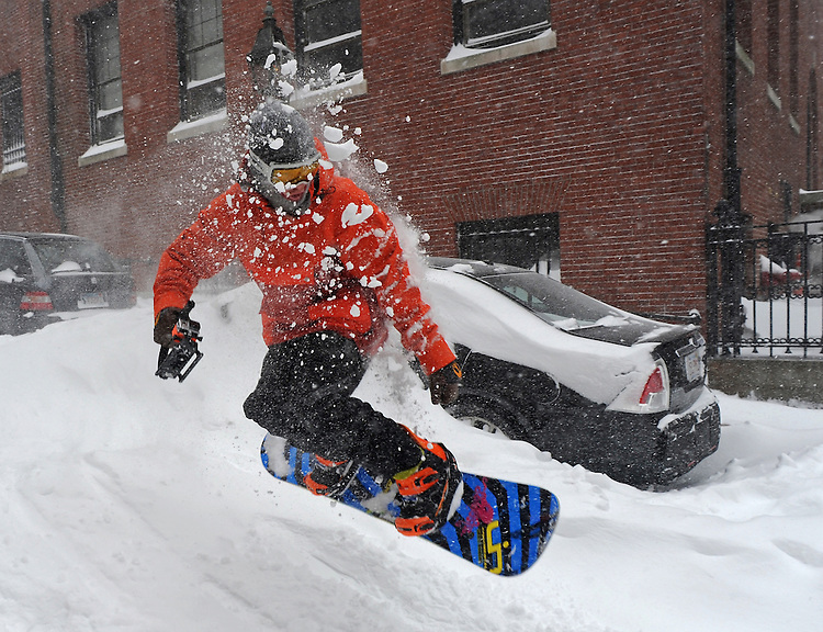 A snowboarder catches some air in Boston's Beacon Hill section after a blizzard dumped over two feet of snow in the city on Tuesday, January 27, 2015. Photo by Christopher Evans