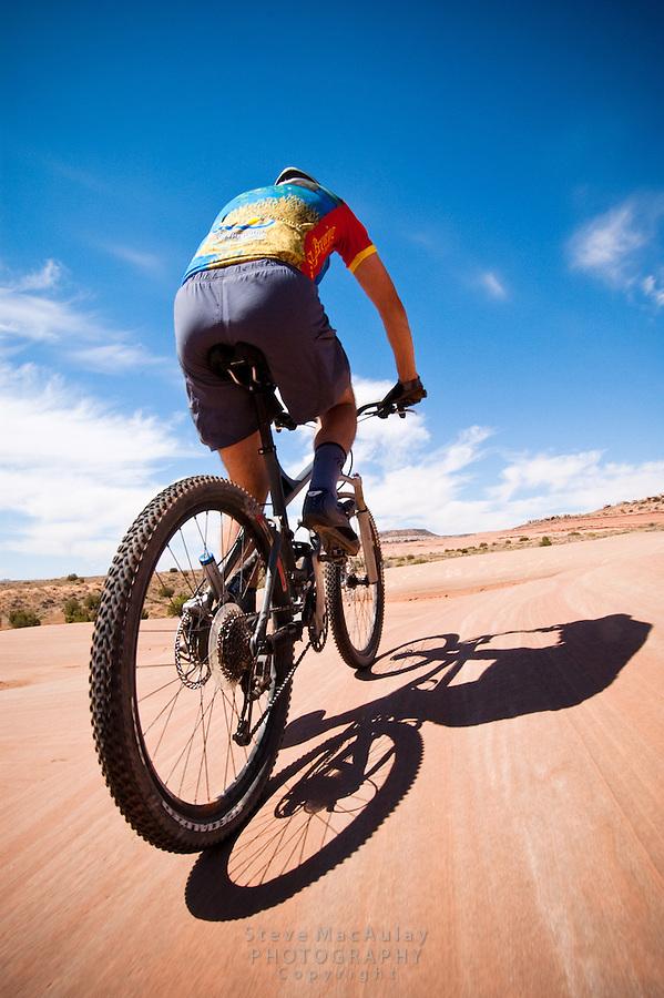 Male mountain biker on the striated slickrock dunes of Bartlet Wash, Moab, Utah