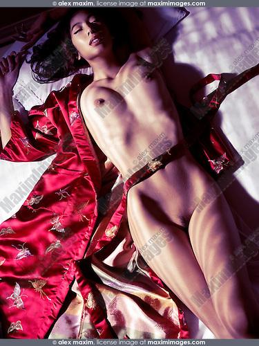 Beautiful nude asian woman in red kimono lying in bed in dramatic dim light