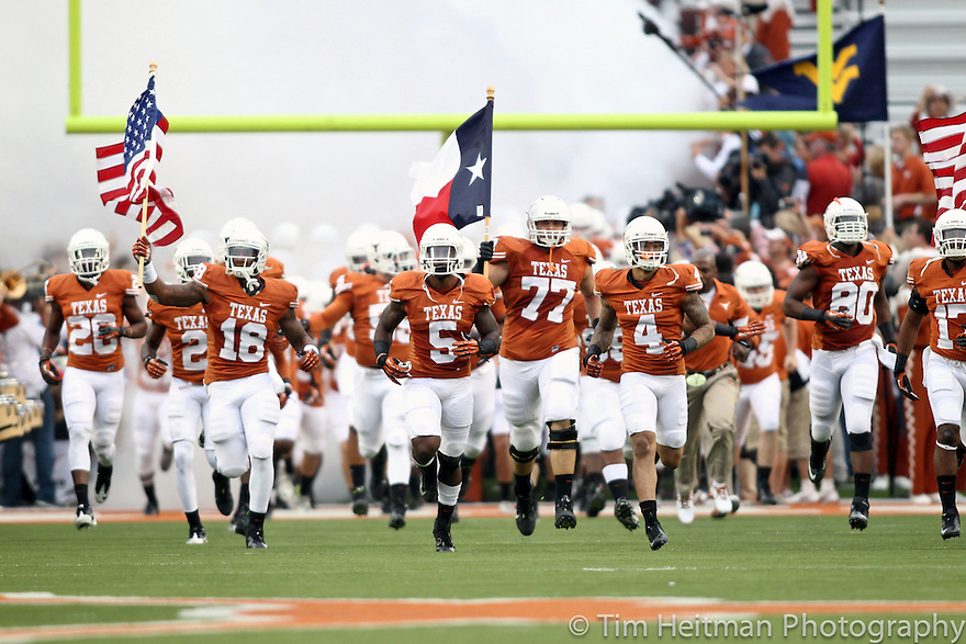 Oct 6, 2012; Austin, TX, USA; Texas Longhorns team runs onto the field carrying flags before the game against the West Virginia Mountaineers at Darrell K Royal-Texas Memorial Stadium. West Virginia beat Texas 48-45. Mandatory Credit: Tim Heitman-US PRESSWIRE