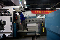 Plant workers adjust a new printing press in the new Bible printing facility for the Amity Printing Company in Nanjing, China... The Amity Printing Company is the only company allowed to publish Christian Bibles in China and, with this new printing facility scheduled to open in May 2008, is the world's largest producer of Bibles.  The Amity Foundation, the Chinese charity which oversees the Amity Printing Company, was founded in 1985 with the express purpose of promoting education, health, social welfare, and rural development in China.