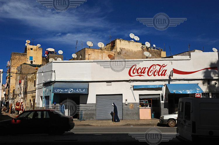 A man in  a burnoose walks past a Coca Cola advertisemnet painted on a shop front. The roofs above the shop are lined with satellite dishes.
