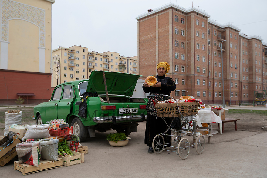 Uzbekistan - Tashkent - A street seller shows a traditional bread as she stands next to a Moskvich in the streets of Sergeli, the largest working class neighborhood of the capital.
