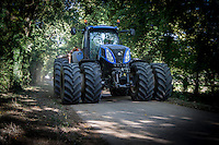 New Holland tractor with front and rear dual wheels on the road