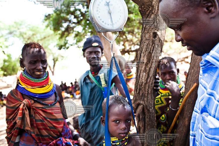 50 year old Etokoit Nachukuli (left) looks on while a Merlin NGO nurse measures the weight of her 28 month old malnourished girl Ekuri Nachukuli from the Turkana tribe in Nakapelewoi village.