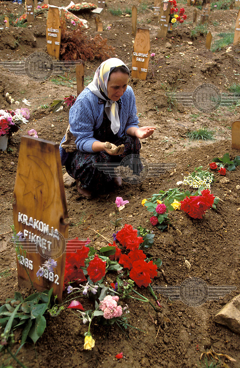 The siege of Sarajevo. Woman praying at the graveside of a victim of the fighting.  .Around 250,000 people died in the civil war between Bosnian Muslims, Croats and Serbs in the years 1992-1995, part of the break-up of the former Yugoslavia.
