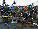 2:01PM, March 16, 2011, Soma, Fukushima Prefecture, Japan - Firemen search for survivors in the rubble of a house after the Tohoku-Kanto Natural Disaster (Photo by Mainichi Newspaper)